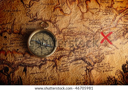 Old brass compass lying on a very old map showing the way to treasure - stock photo