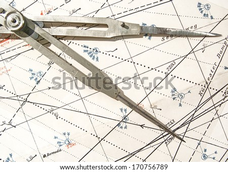 Old brass dividers on a nautical chart - stock photo