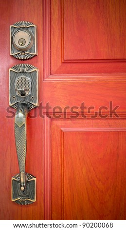 Old brass handle on orange wood door. - stock photo