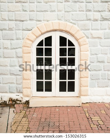 old brick and stone wall with door to the house - stock photo