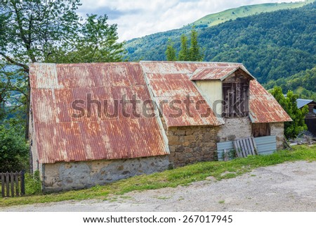 Old brick barn with a rusty corrugated galvanised iron roof - stock photo