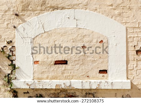 old brick  brick wall with broken plaster and plants growing through the cracks - stock photo