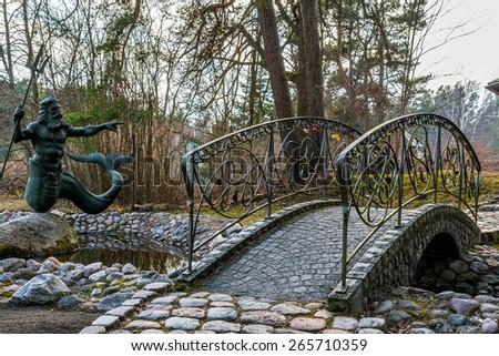 Old brick bridge and statue of Poseidon in Latvia - stock photo