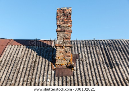 old brick chimney on the roof of a village house - stock photo