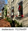 Old brick colonial house decorated for Christmas with wreath on door - stock photo