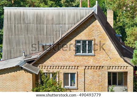 old brick house. old roof slates and chimney. old windows