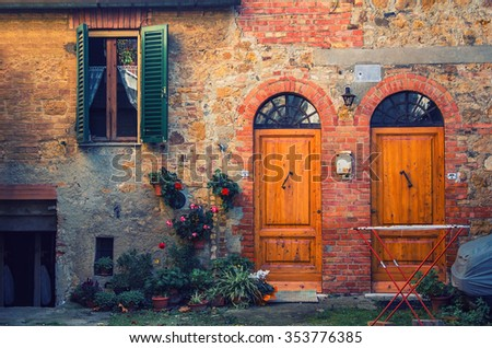 old brick italian facade stylized vintage hipster with two doors and a window - stock photo