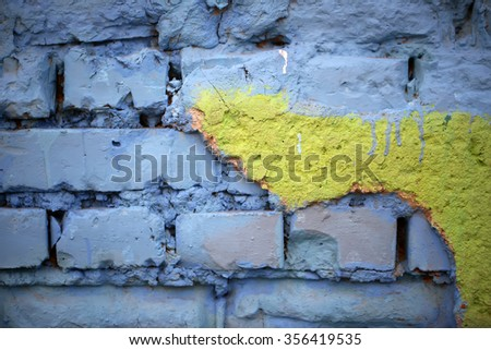 Old brick rough wall painted by blue and yellow paints Ukrainian state colors of flag textured wallpaper banner design natural background copyspace closeup, horizontal picture  - stock photo