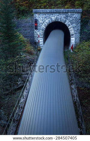 Old brick tunnel in the mountains and incoming train with long exposure - stock photo
