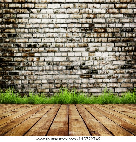 Old brick wall and green grass on wood floor background - stock photo