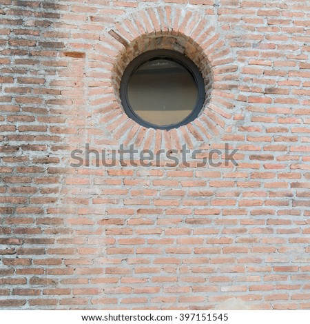 Old brick wall background and round window glass - stock photo