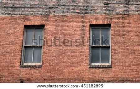 Old brick wall background exterior with windows - stock photo