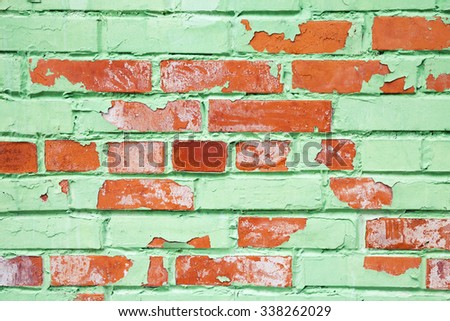 Old brick wall closeup texture with damaged layer of green paint, background photo - stock photo
