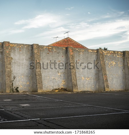 Old brick wall in an outdoor parking lot. - stock photo