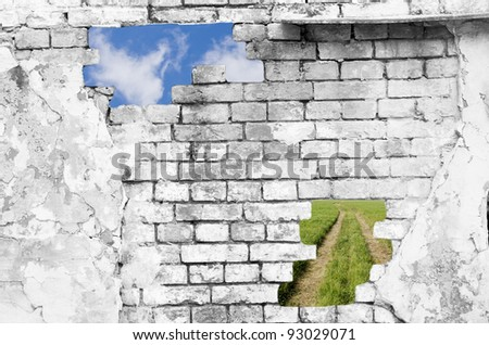 Old brick wall in black and white (with blue sky and lane across a green field showing through the holes) - stock photo