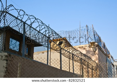 Old brick wall of prison with barbwire background