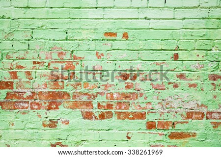 Old brick wall texture with damaged layer of green paint, background photo - stock photo