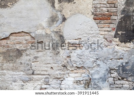 Old brick wall with damaged stucco and paint layers, closeup background photo texture - stock photo