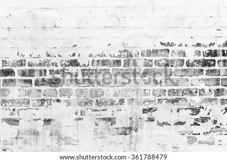 Old brick wall with damaged white paint layer, closeup background photo texture - stock photo