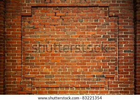 Old brick wall with decorative bricks forming an internal frame - stock photo