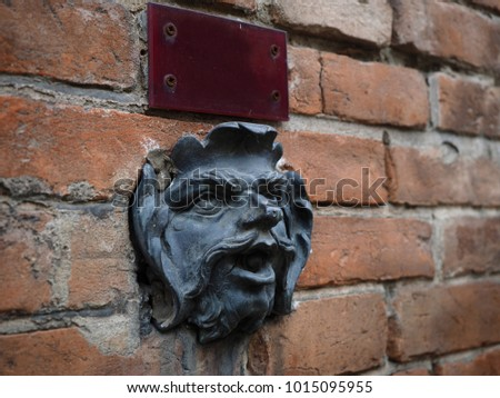 Old Brick Wall With Door Bell In The Shape Of A Manu0027s Head And A Name
