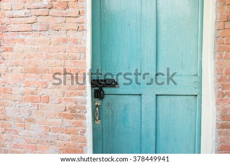 Old brick wall with green doors