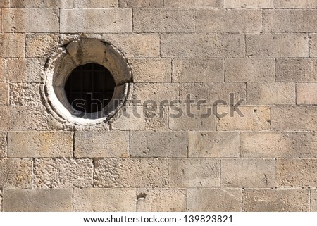 Old brick wall with round window - stock photo
