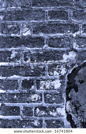 Old brick wall with stucco splotches. Dark blue toned - stock photo