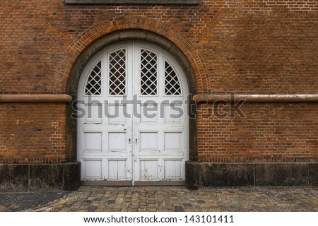 Old Brick Wall with white door - stock photo