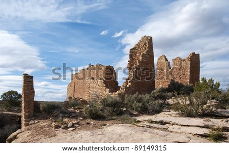 Old brick walls of an ancient Native American structure at Hovenweep National Monument in Utah under a vast partly cloudy sky - stock photo