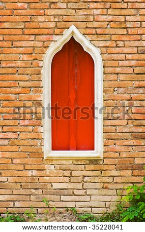 old brickwall with a wooden red window in the center - stock photo