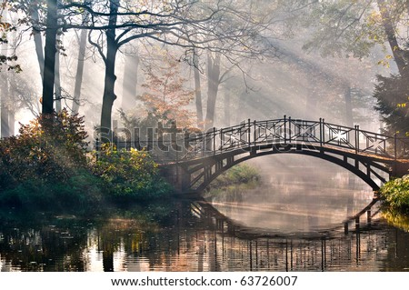 Old bridge in autumn misty park - HDR - stock photo
