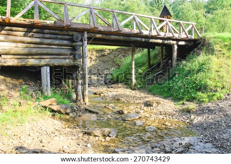 Old bridge over the forest stream in hot summer day - stock photo
