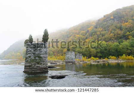 old bridge supports in the Potomac River at Harpers Ferry National Historical Park - stock photo