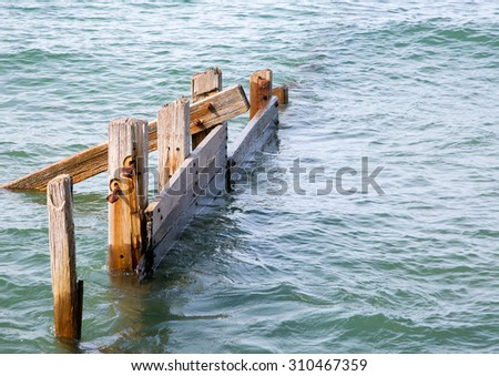 Old broken and weathered wooden breakwaters - stock photo