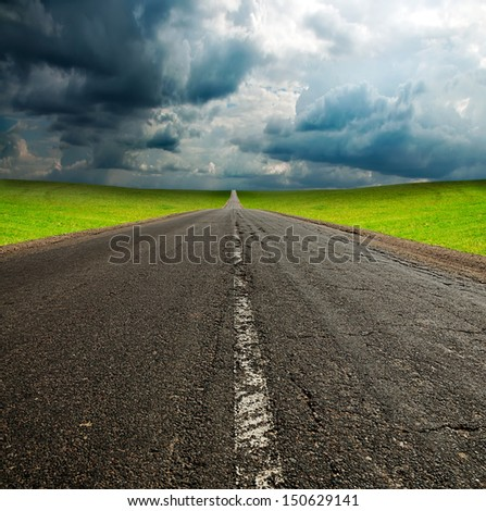 old broken asphault road in green field over blue cloudy sky - stock photo