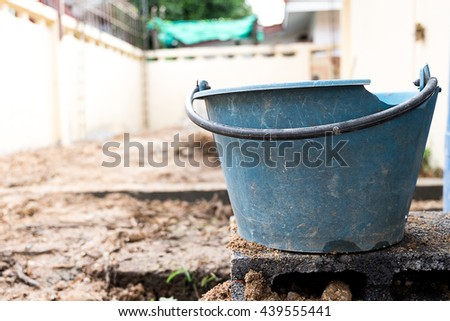 Old broken blue bucket on cement