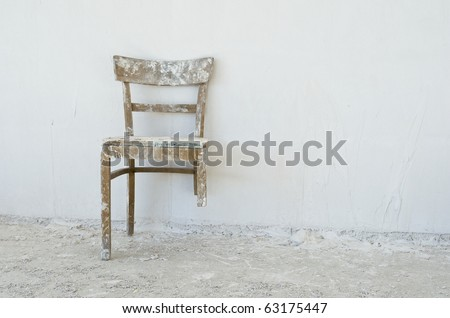 Old broken chair at a construction site - stock photo