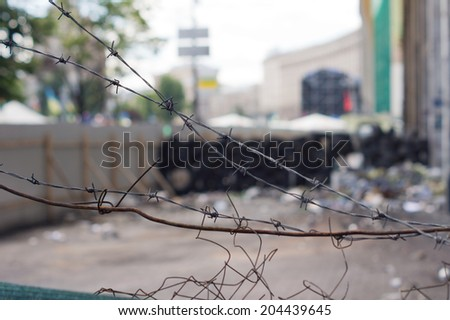 Old broken diamond mesh fence with broken corroded rusty strands of wire surrounding a litter filled yard - stock photo