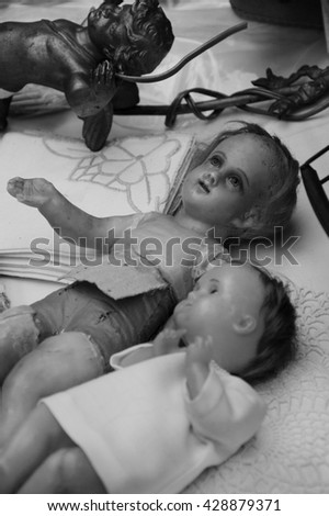 Old broken dolls at flea market. Child abuse concept. Selective focus. Black and white photo. - stock photo
