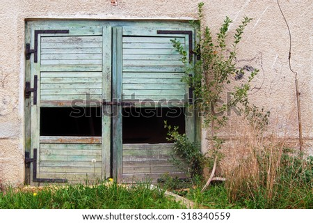 Old broken door in the middle of nature - stock photo