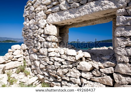 Old broken down house on the coast of Croatia with a view through the stone wall window. - stock photo