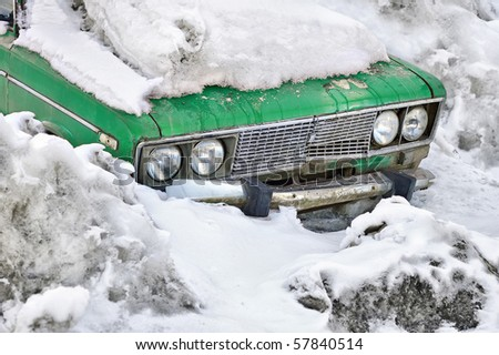 Old broken green car in snow