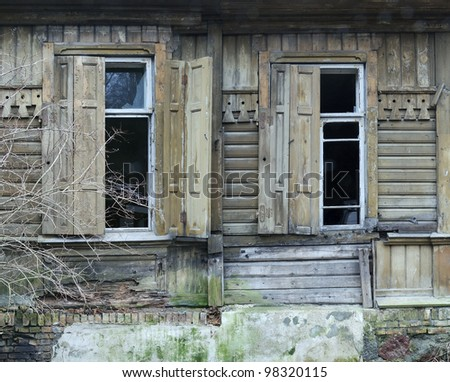 Old broken house in spring, damaged windows and sun-blinds
