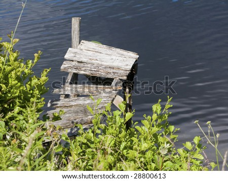 Old broken jetty at the lake - stock photo