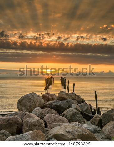 Old broken pier at colorful dawn, Baltic Sea - stock photo