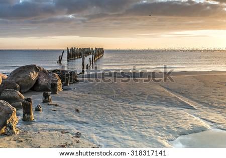 Old broken pier at sandy beach of the Baltic sea, Latvia, Europe - stock photo