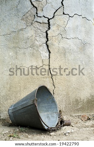 Old broken scuttle in front of cracked wall of well - stock photo