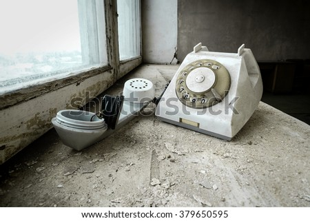 Old broken telephone on a windowsill of an abandoned office - stock photo