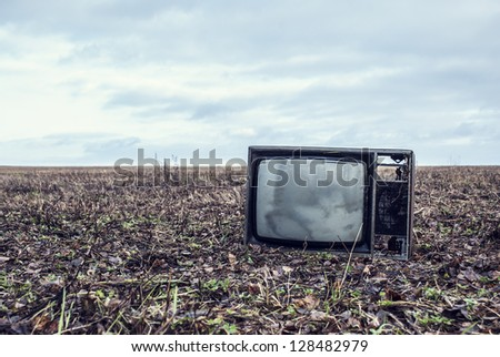 old broken TV is an autumn field - stock photo